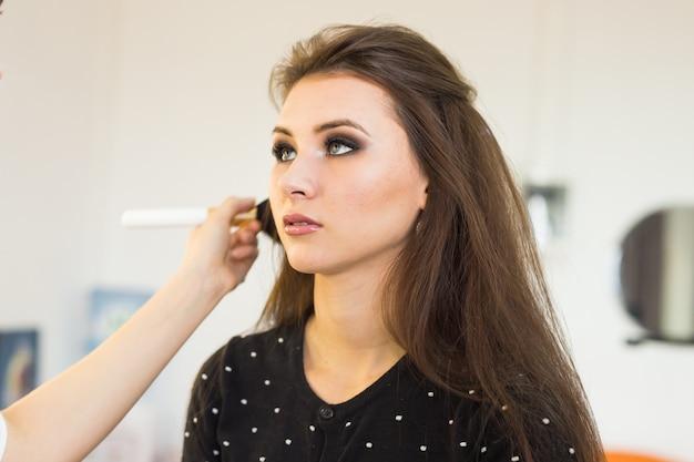 Make-up-artist macht make-up für junge schöne braut, die hochzeits-make-up aufträgt