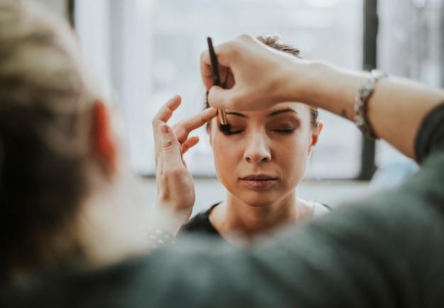 Make-up-artist trägt lidschatten auf das modell auf