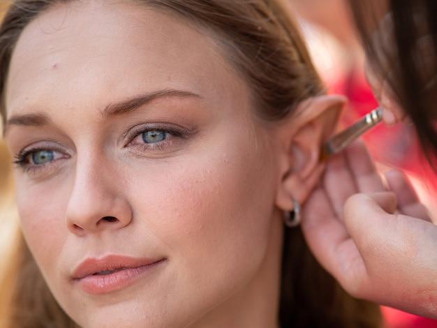Make-up auf den ohren zu einem model, um sie in eine elfe zu verwandeln