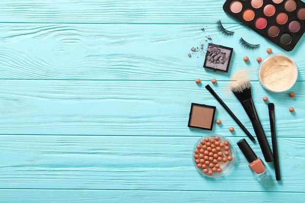 Make-up auf einem blauen hölzernen hintergrund. platz für text