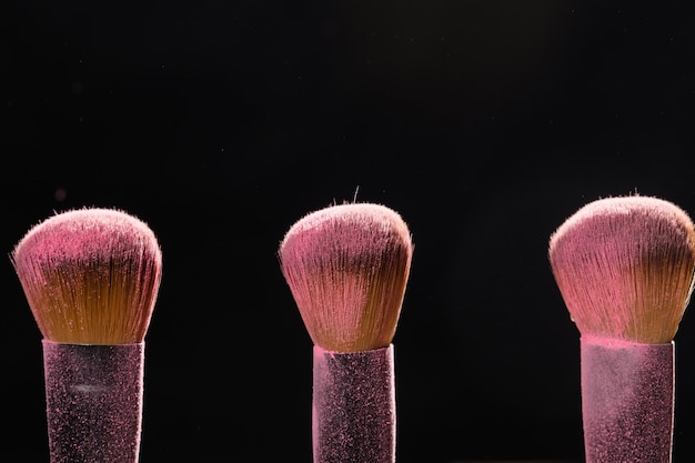 Make-up, beauty und mineral kosmetik konzept pinsel mit rosa puder über die schwarze wand
