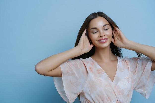 Make-up, beauty und modekonzept. porträt der entspannten schönen frau hält haare, steht mit geschlossenen augen, erinnert an etwas angenehmes, trägt modisches kleid.