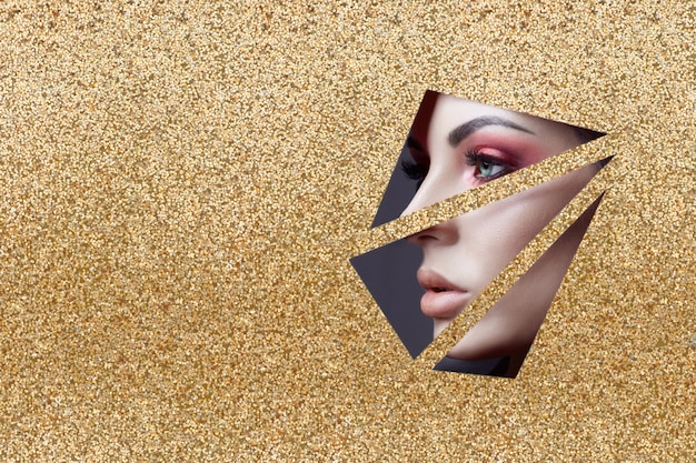 Make-up des roten auges des schönheitsgesichtes eines jungen mädchens in einem schlitzloch des gelbgoldpapiers. frau mit rotem glühendem schatten des schönen make-up, pralle lippen, farbe der großen augen im goldenen schlitzloch