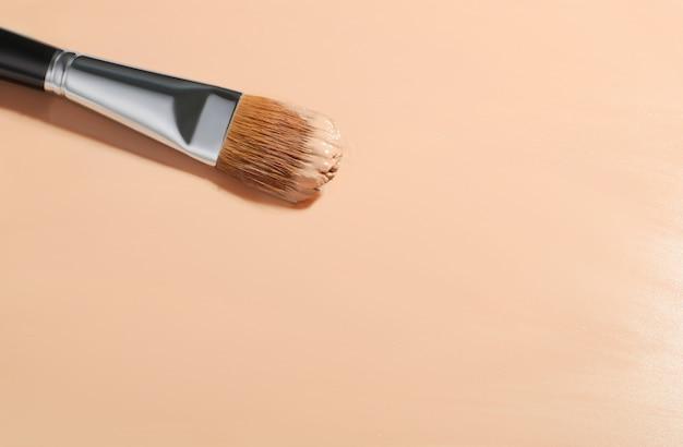 Make-up foundation hintergrund mit beiger flüssiger foundation, kosmetischer make-up pinsel, fluid foundation base für nackte haut
