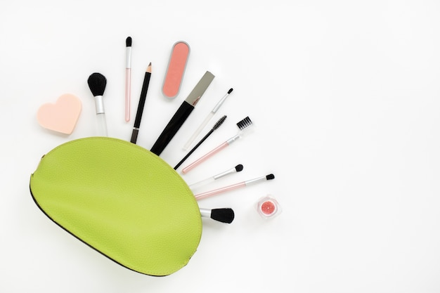 Make-up-kosmetik in einer hellgrünen kosmetikerin auf weiß