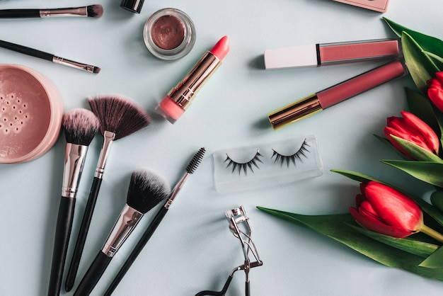 Make-up-kosmetik-set und rote pfingstrosenblüten