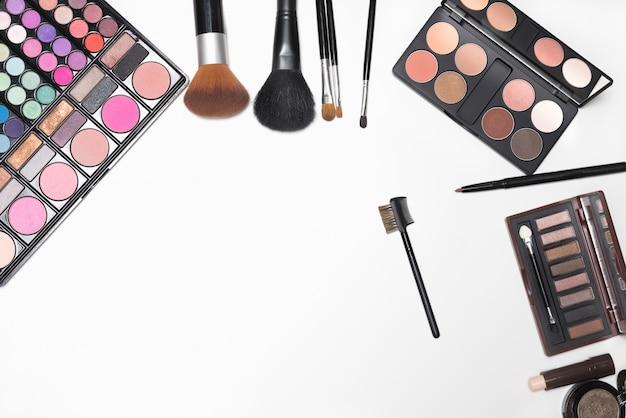 Make-up kosmetik und pinsel auf weißem hintergrund mit kopie platz für text