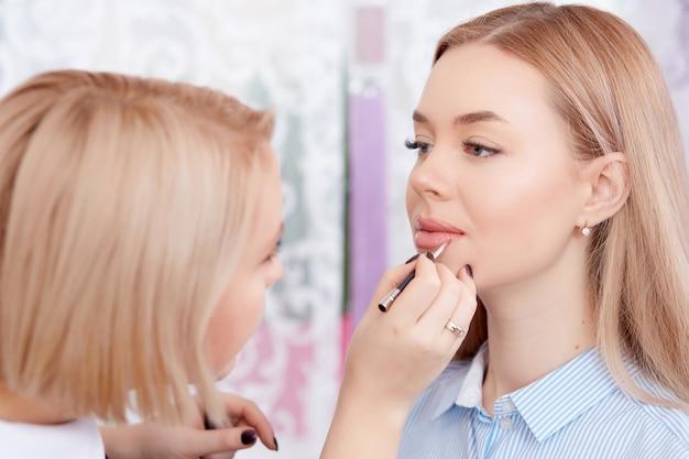 Make-up-künstler machen make-up von lippen.