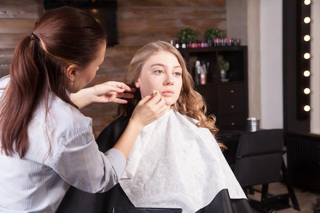 Make-up-künstlerin, die eine junge frau professionell schminkt