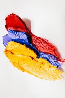 Make-up-kunst. dekorative kosmetik. gelbe blaue rote lippenstiftproben auf weißem hintergrund.