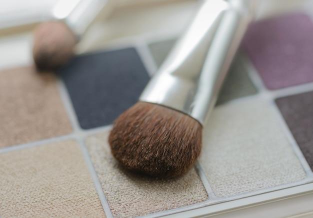 Make-up-lidschatten-set und pinsel nahaufnahme hintergrund. flacher dof