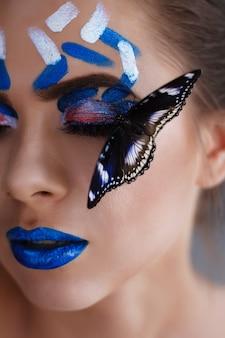 Make-up nahaufnahme. blaue lippen. ein schmetterling sitzt auf dem gesicht des mädchens