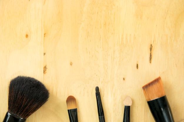 Make-up pinsel auf holz hintergrund. schönheitsprodukte, draufsicht, flaches lagebegriff.