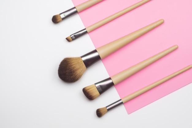 Make-up pinsel auf weißem und rosa hintergrund