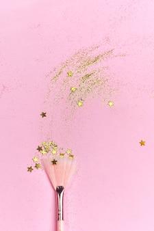 Make-up pinsel, goldene schimmer und leuchtende sterne auf rosa oberfläche streuen
