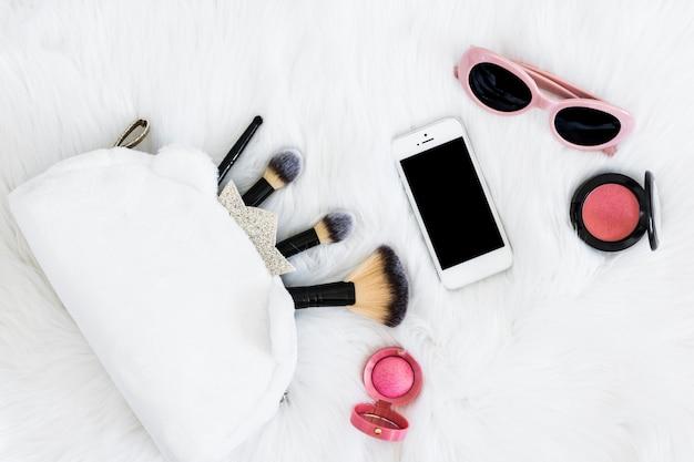Make-up-pinsel in der tasche; mobiltelefon; sonnenbrille und rosa kompaktes gesichtspuder auf weißem fell