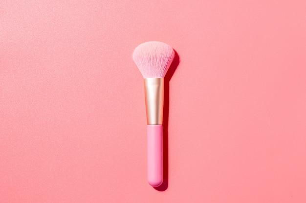 Make-up pinsel mit puder auf rosa oberfläche