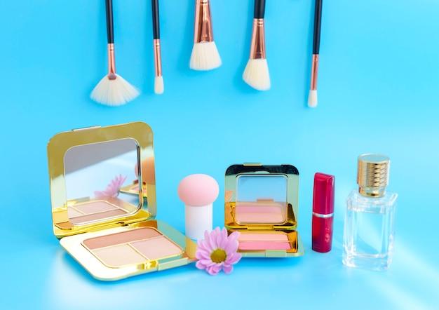 Make-up pinsel, roter lippenstift, eine flasche parfüm und rougepads