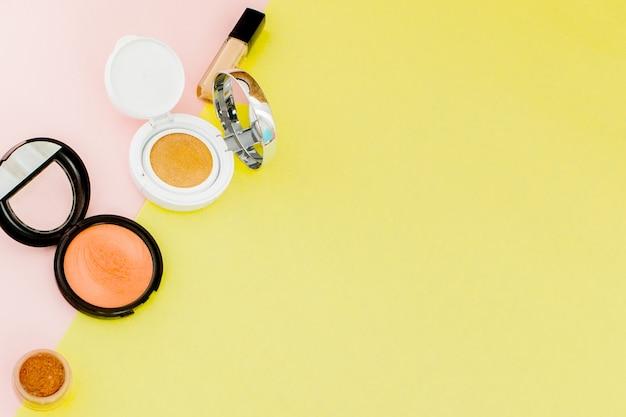 Make-up-produkte auf einem leuchtend gelben und rosa hintergrund mit kopierraum, minimalem stil