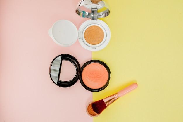 Make-up-produkte auf einem leuchtend gelben und rosa hintergrund pink