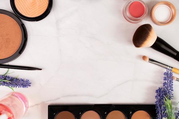 Make-up-produkte, kosmetika, pinsel, schatten auf einer weißen hintergrund-draufsicht mit platz für text, kopierraum