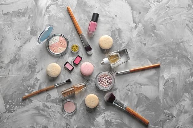 Make-up-produkte und makronen auf grauem strukturiertem hintergrund Premium Fotos