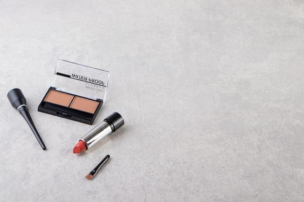Make-up puder in schwarzer runder plastikhülle mit lippenstift und pinseln.
