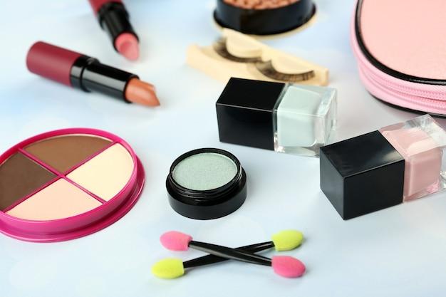 Make-up-set mit kosmetikerin, falschen wimpern und kosmetika auf blau verschwommener oberfläche Premium Fotos