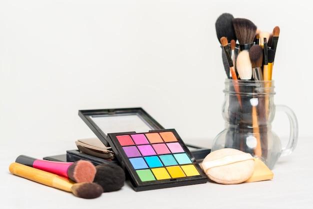 Make-up und beauty-konzept. bunte kosmetik auf platte mit bürsten auf tabelle.