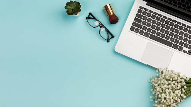 Make-upbürste, brillen, blumenstrauß der weißen blume der kaktuspflanze mit laptop auf blauem hintergrund