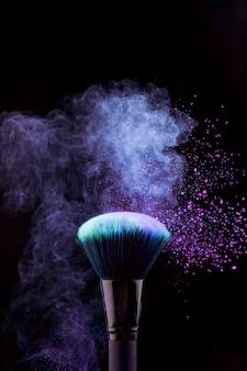 Make-upbürste mit blauem puderspritzen