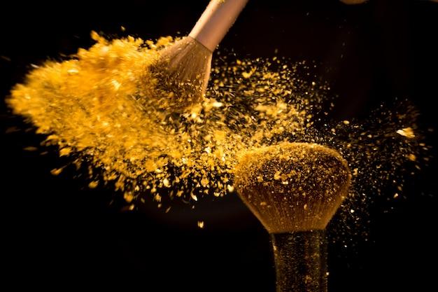 Make-upbürste mit dem goldenen kosmetischen puder, das auf schwarzem hintergrund verbreitet