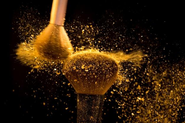 Make-upbürste mit dem goldenen kosmetischen pulver, das auf schwarzen hintergrund verbreitet