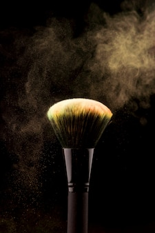 Make-upbürste mit gelbem puderspritzen