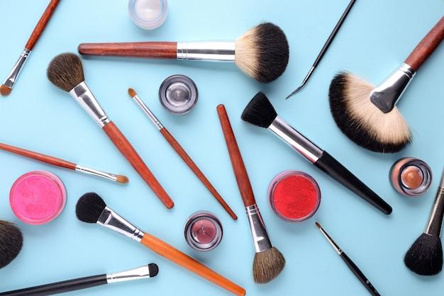 Make-upbürsten und -kosmetik auf einem blauen hintergrund. draufsicht, flach zu legen
