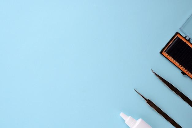 Make-upbürsten und -kosmetik auf einem blauen hintergrund. draufsicht, flache lage, kopienraum