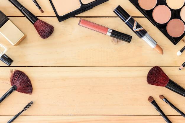 Make-upkosmetik auf holztischhintergrund mit textraum, über licht, draufsicht