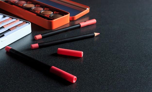 Make-upkosmetik auf schwarzem tabellenhintergrund, über licht, draufsicht