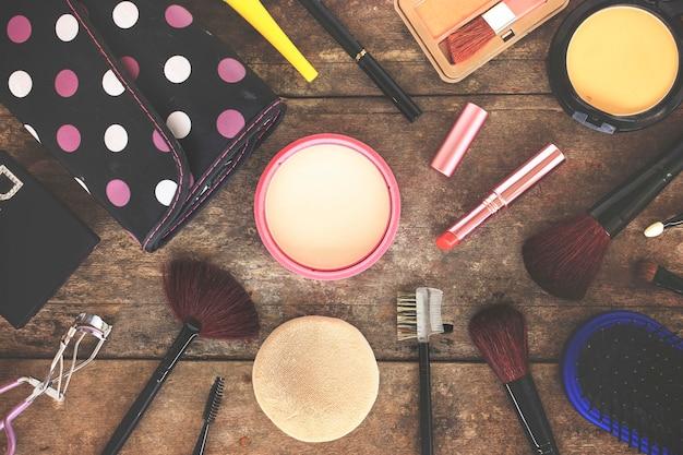 Make-upkosmetik und -bürsten auf holztischhintergrund