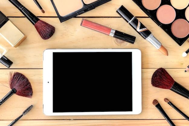 Make-upkosmetik und tablet-computer auf holztisch