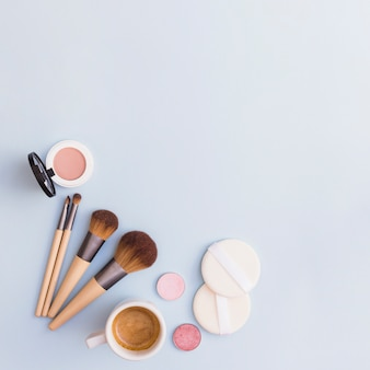 Makeup bürsten; lidschatten; rouge und schwamm mit kaffeetasse auf blauem hintergrund