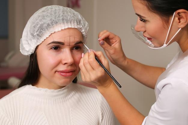Makeup eyebrows master bereitet das liniendesign vor. assistent lernt modell. weiße uniform, steril. architektur mit werkzeugen.