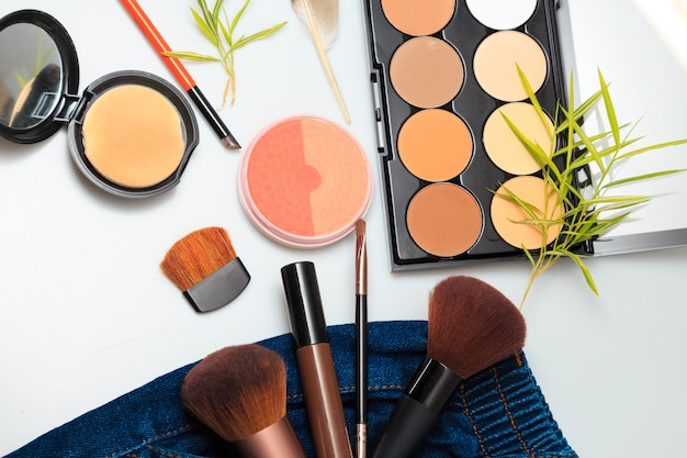 Makeup-produkte und kosmetische schönheitsprodukte, die heraus von denimjeans der frau verschüttet werden