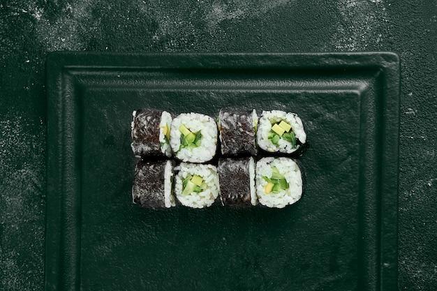 Maki-sushi-rolle mit gurke. klassische japanische küche. lebensmittellieferservice. schwarzer hintergrund