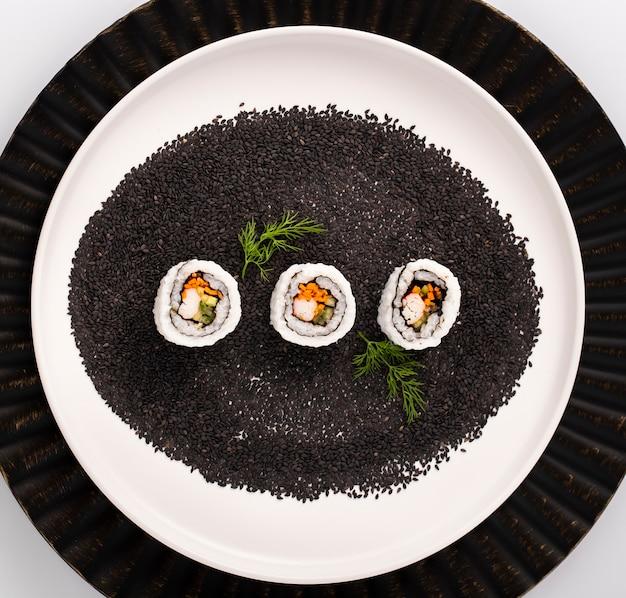Maki-sushirollen auf samen des schwarzen indischen sesams
