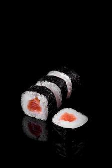 Makis thunfisch-sushi auf schwarzem hintergrund. asiatisches essen