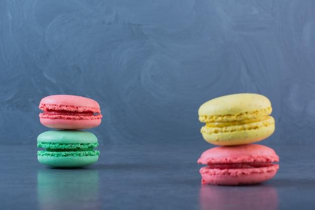 Makkaroni-kekse in verschiedenen farben auf einer dunkelgrauen oberfläche