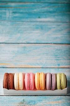 Makkaroni-kekse verschiedener farben in einer schachtel auf einem blauen, alten hölzernen hintergrund der blauen farbe.