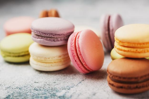 Makkaroni-kekse verschiedener farben in einer schachtel auf einem grauen strukturierten hintergrund aus stein freiraum.