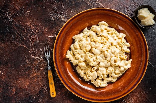 Makkaroni mac und käse mit cheddar-sauce in einem teller.
